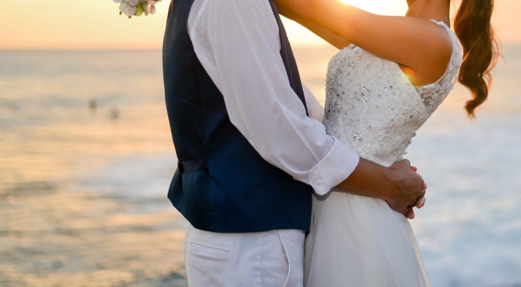 夕日の海辺で抱き合う男女の画像