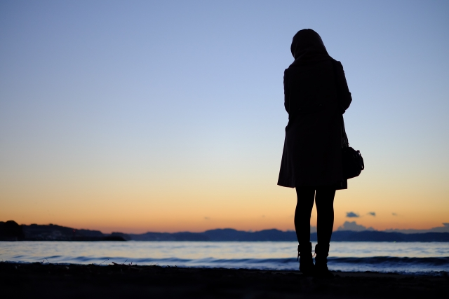 独り水辺にたたずむ女性の画像