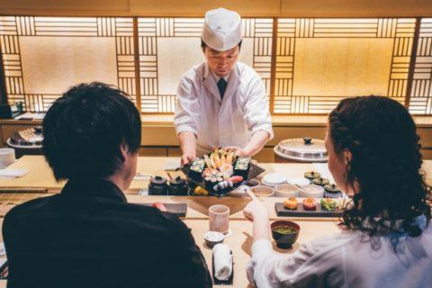 お寿司屋さんで食事をする男女ののイメージ画像