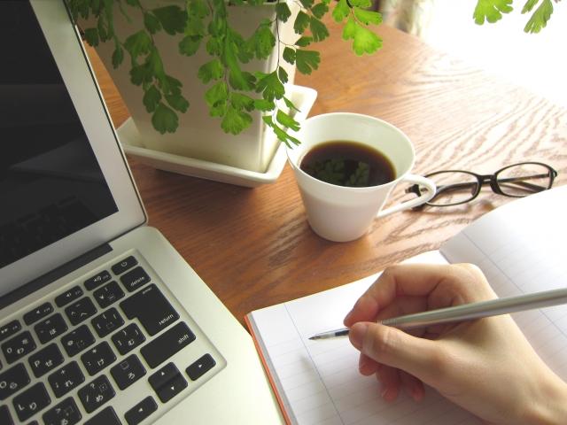 スキルアップのためにパソコンを見ながらメモをとる人のイメージ画像